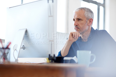 Buy stock photo Low angle view of a mature professional man looking intently at his pc