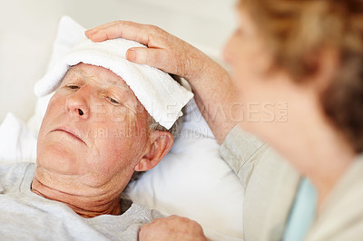 Buy stock photo Cropped shot of a senior woman applying a cold compress to her sick husband's forehead