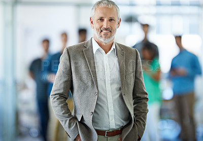 Buy stock photo Portrait of a mature businessman standing in an office with colleagues in the background