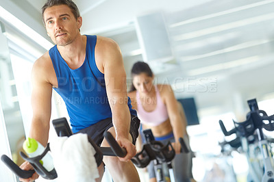 Buy stock photo A man and woman exercising in spinning class at the gym