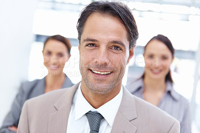 Buy stock photo Smiling mature business with his coworkers behind him - portrait