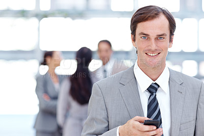 Buy stock photo Smiling young businessman using his mobile - portrait