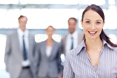 Buy stock photo Attractive businesswoman smiling with her coworkers standing behind her