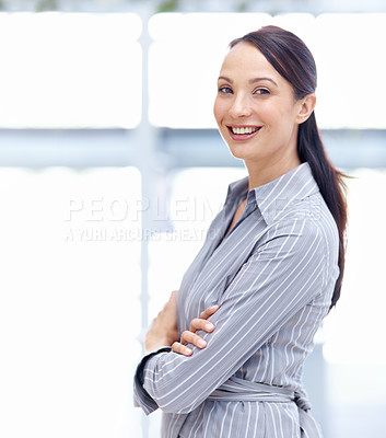 Buy stock photo Portrait of a positive young businesswoman smiling while standing with her arms folded
