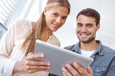 Buy stock photo Low angle portrait of two young office workers looking at a digital tablet together
