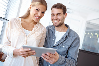 Buy stock photo Low angle portrait of two positive-looking young office workers looking at a digital tablet together