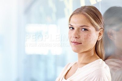 Buy stock photo Portrait of a young business professional leaning against a glass wall and looking at the camera