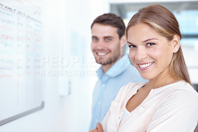 Buy stock photo Portrait of two young business professionals standing in the office and looking at a whiteboard