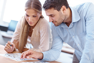 Buy stock photo Shot of two young design professionals sitting at a table editing photographs