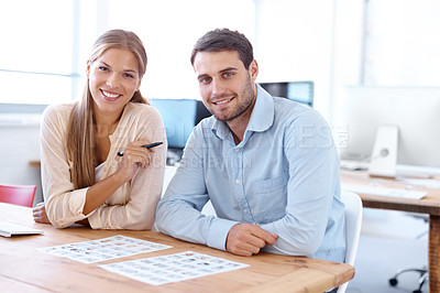 Buy stock photo Portrait of two positive-looking young designers at work in the office