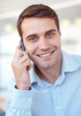 Buy stock photo Closeup portrait of a handsome young business professional talking on a mobile phone