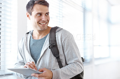 Buy stock photo Shot of a male university student standing in a hallway working on a digital tablet