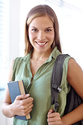 Buy stock photo Portrait of a female university student carrying a book and smiling at the camera