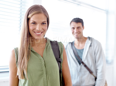 Buy stock photo Portrait of two confident young university students standing in a hallway and smiling at the camera