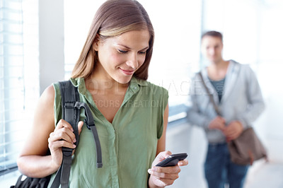 Buy stock photo Shot of a female university student texting on a cellphone with a male student standing in the background