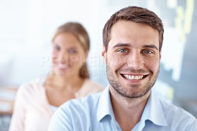 Buy stock photo Handsome young businessman smiling at the camera with his female colleague in the background