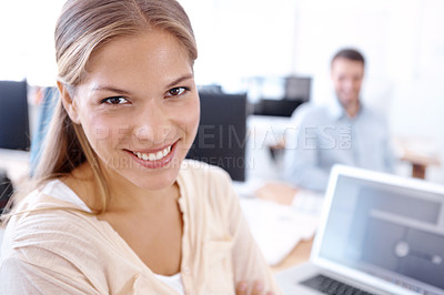 Buy stock photo Lovely young businesswoman sitting at her desk with her co-worker in the background - portrait