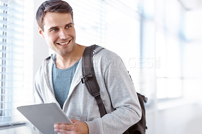 Buy stock photo Young male student with a backpack and a digital tablet walking down the hallway
