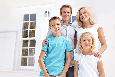 Buy stock photo A loving family of four standing in front of their house