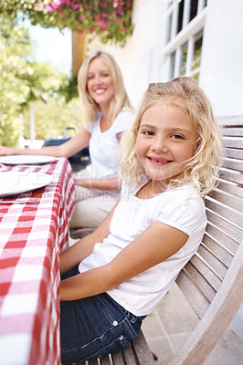 Buy stock photo A cute young girl having lunch with her family outdoors