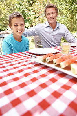 Buy stock photo A father and son sitting at the lunch table together on a summer's day