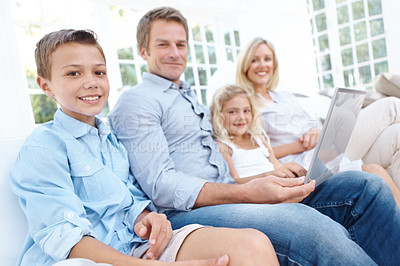 Buy stock photo A young boy using a laptop with his family in the lounge
