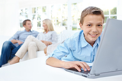 Buy stock photo A young boy using a laptop while his parents are blurred in the background
