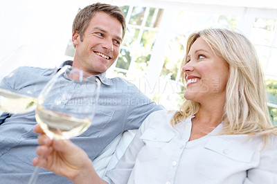 Buy stock photo A mature couple enjoying a glass of wine together in their lounge