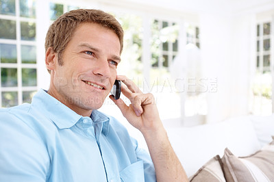 Buy stock photo A handsome modern man talking on his cellphone while in his lounge