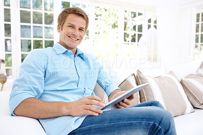 Buy stock photo Portrait of a handsome mature man using a digital tablet from the comfort of home