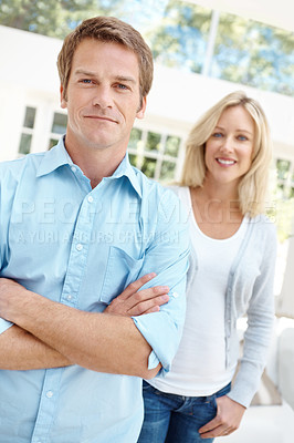 Buy stock photo A handsome mature man crossing his arms with his wife in the background