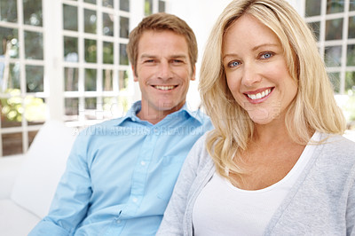 Buy stock photo A comfortable mature couple sitting on their couch together happily
