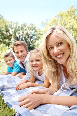 Buy stock photo Portrait of a happy family sitting on a picnic blanket in a park