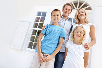 Buy stock photo A happy family standing outside their front door with copyspace