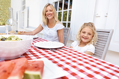 Buy stock photo A  portrait of a mother and daughter sitting at the table for lunch
