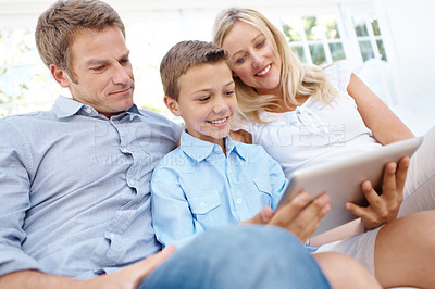 Buy stock photo A happy family sitting on their couch looking at a digital tablet