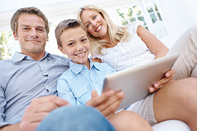 Buy stock photo Portrait of a happy family sitting on the couch with their son holding a digital tablet