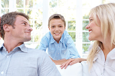 Buy stock photo A smiling mother and father looking adoringly at their son