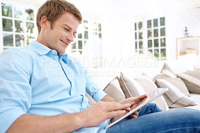 Buy stock photo A man sitting on his couch and smiling while playing with his new digital tablet
