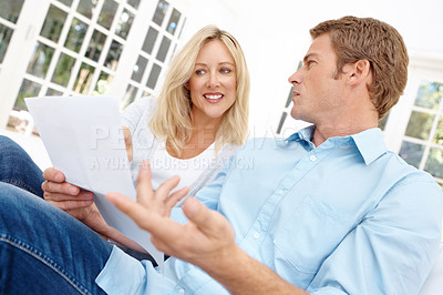 Buy stock photo A couple sitting on a couch while the man asks about the paper he is holding