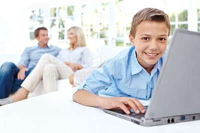 Buy stock photo Cute little boy using a laptop with his parents in the background