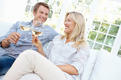 Buy stock photo Happy mature couple toasting to each other with white wine