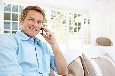 Buy stock photo Handsome mature man making a call from his mobile while at home