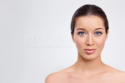 Buy stock photo Gorgeous young woman with perfect skin looking at you against a gray background