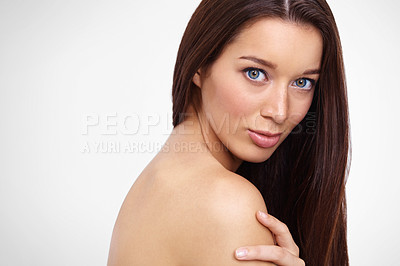 Buy stock photo Cropped view of a beautiful young woman with long brown hair and flawless skin looking at you against a gray background