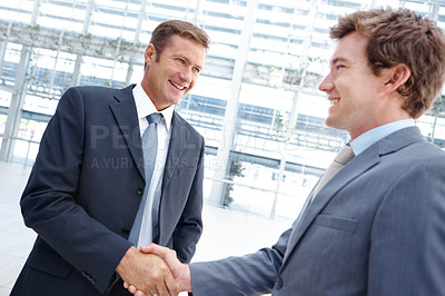 Buy stock photo Two businessmen reaching an agreement with a solid handshake