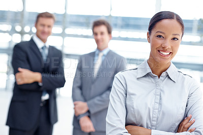 Buy stock photo An ambitious business woman standing with her colleagues blurred in the background