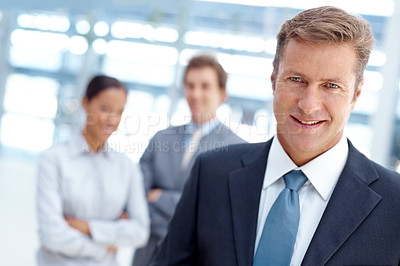 Buy stock photo A handsome businessman smiling at the camera with two colleagues standing in the background
