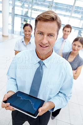 Buy stock photo A handsome businessman standing with a digital tablet in hand and his team in the background