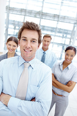 Buy stock photo A handsome young businessman standing with his arms folded with his colleagues in the background
